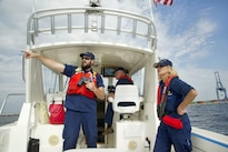 Coast Guard auxiliary members Tim Clarke, left, Don Parker, center, and Dorothy Neiman, all assigned to Flotilla 23-03 in Annapolis, Md., maintain a safety zone for an air show during Maryland Fleet Week in Baltimore, Oct. 16, 2016. Coast Guard photo by Petty Officer 2nd Class Lisa Ferdinando