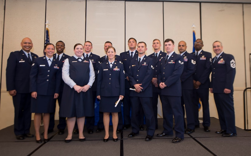 Col. Jimmy Canlas, 437th Airlift Wing commander (far left), and Chief Master Sgt. Kristopher Berg (far right), 437th AW command chief, pose for a group photo with 437th AW Airmen during the fall graduation ceremony for the Community College of the Air Force here Oct. 13, 2016. The CCAF is a federally-chartered, degree-granting institution serving the United States Air Force's enlisted total force.