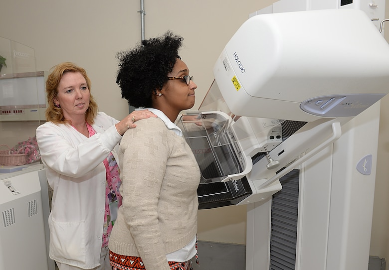 Wendy Elvis, 633rd Surgical Operations Squadron lead mammography technician, demonstrates the use of a mammogram machine with Melissa McRae, 633rd Surgical Operations Squadron command secretary, at Joint Base Langley-Eustis, Va., Oct. 17, 2016. Mammograms are recommended for women over the age of 40 and those whose family has a history of breast cancer. (U.S. Air Force photo by Staff Sgt. Teresa J. Cleveland)