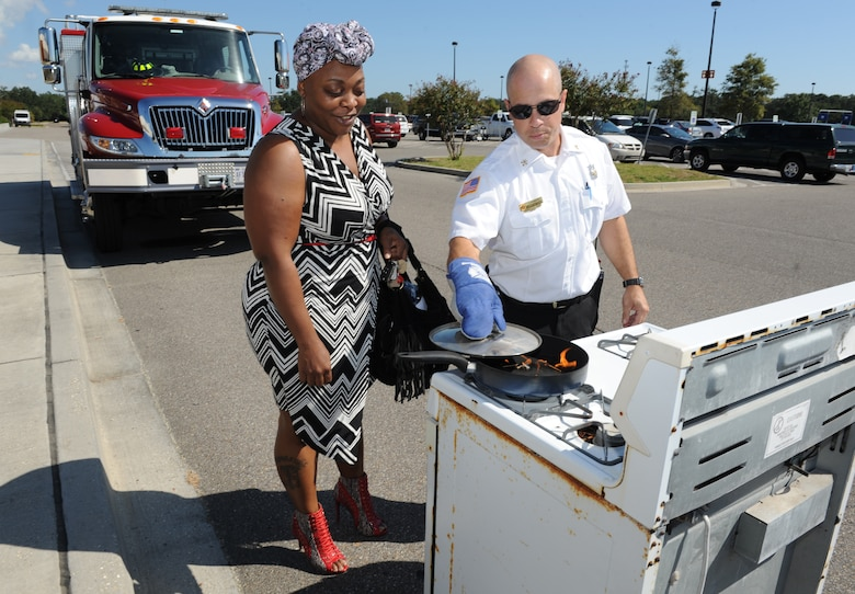 Jason Sanders, 81st Infrastructure Division fire prevention assistant chief, demonstrates how to safely put out a stove fire to Ieasha Sims, Keesler Base Exchange sales associate, during Fire Prevention Week outside of the Base Exchange Oct. 11, 2016, on Keesler Air Force Base, Miss. The week-long event included fire drills, literature hand-outs and stove fire demonstrations around the base and concludes with an open house at the fire department. (U.S. Air Force photo by Kemberly Groue/Released)