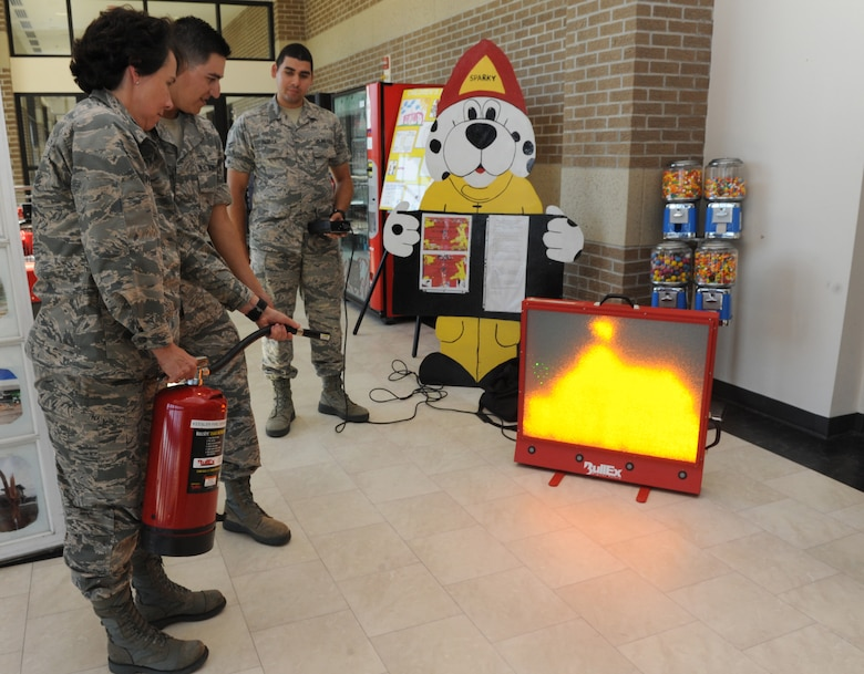 Col. Jeannine Ryder, 81st Medical Group commander, uses an electric fire extinguisher during Fire Prevention Week at the Base Exchange Oct. 11, 2016, on Keesler Air Force Base, Miss. The week-long event included fire drills, literature hand-outs and stove fire demonstrations around the base and concluded with an open house at the fire department. (U.S. Air Force photo by Kemberly Groue/Released)