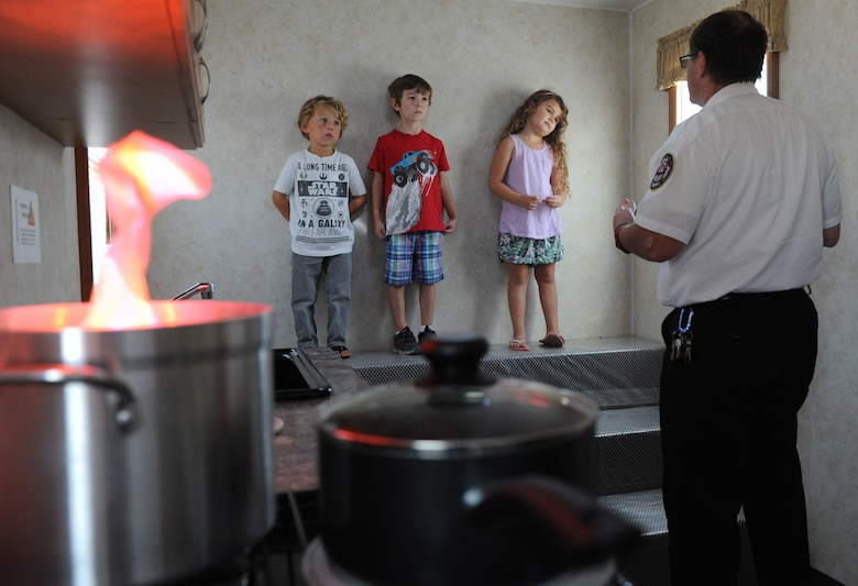 James Shirah, 81st Infrastructure Division fire inspector, shows Keesler children what to do when smoke fills a room during the Fire Prevention Week open house at the Keesler Fire Department Oct. 15, 2016, on Keesler Air Force Base, Miss. Throughout the week the Keesler Fire Department conducted fire drills, toured various facilities with Sparky the Fire Dog, passed out fire safety information and fire hats for children and provided stove and fire extinguisher demonstrations. (U.S. Air Force photo by Kemberly Groue/Released)