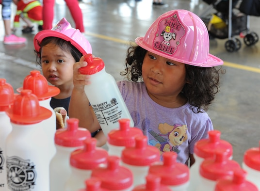 Zoe and Ivy Macias, daughters of Staff Sgt. Cameron Macias, 331st Recruiting Squadron recruiter, Slidell, La., collect gifts during the Fire Prevention Week open house at the Keesler Fire Department Oct. 15, 2016, on Keesler Air Force Base, Miss. Throughout the week the Keesler Fire Department conducted fire drills, toured various facilities with Sparky the Fire Dog, passed out fire safety information and fire hats for children and provided stove and fire extinguisher demonstrations. (U.S. Air Force photo by Kemberly Groue/Released)
