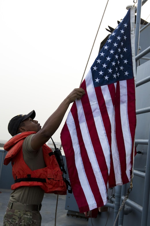 Sgt. Malcom Hilbert, a food service specialist from the 411th Transportation Detachment and a Tupelo, Miss. resident, raised the flag on the MG Charles P. Gross (Logistics Support Vessel-5) during a range exercise in the Arabian Gulf, October 3, 2016. The ship supports the U.S. Army Central mission to move cargo and large vehicles throughout the Middle East from Kuwait Naval Base. (U.S. Army photo by Sgt. Brandon Hubbard, USARCENT Public Affairs)