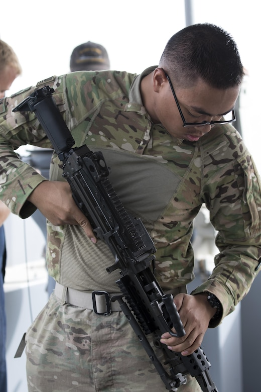 Pfc. Bunnath Chhun, from the 3rd Armored Brigade Combat Team, 1st Infantry Division and a Sheridan, Ind. native, inspects a M249 Squad Automatic Weapon before it is used for range training on the MG Charles P. Gross (Logistics Support Vessel-5) in the Arabian Gulf, October 3, 2016. The ship is part of the large logistics network U.S. Army Central uses to move vehicles and equipment throughout the Central Command theater. (U.S. Army photo by Sgt. Brandon Hubbard, USARCENT Public Affairs)