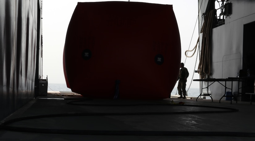 """A Soldier from the 411th Transportation Detachment stands next to a """"Killer Tomato"""" inflatable target on the MG Charles P. Gross (Logistics Support Vessel-5) traveling into international waters in the Arabian Gulf, October 3, 2016. The unit, from Fort Eustis, Va. and based at Kuwait Naval Base, fire crew-served weapons at the targets about four times per year to maintain defensive readiness. (U.S. Army photo by Sgt. Brandon Hubbard, USARCENT Public Affairs)"""