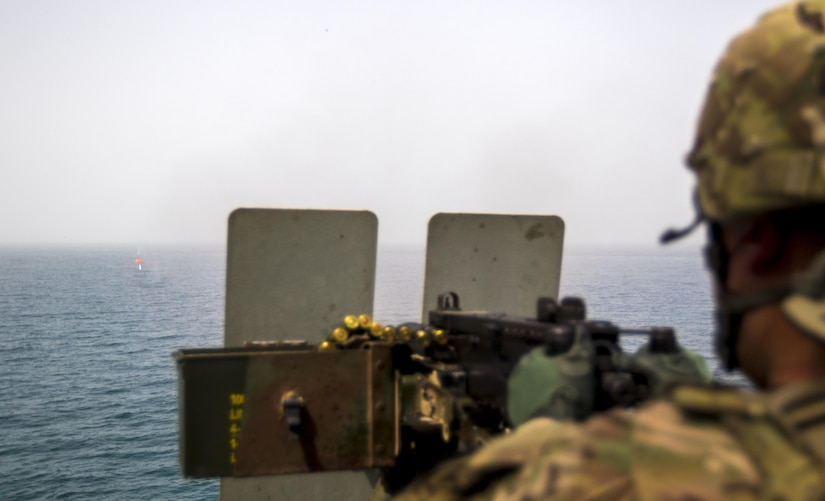 """Pfc. Bunnath Chhun, from the 3rd Armored Brigade Combat Team, 1st Infantry Division and a Sheridan, Ind. Native, fires a .50 caliber machine gun at a """"Killer Tomato"""" target from the MG Charles P. Gross (Logistics Support Vessel-5) in the Arabian Gulf, October 3, 2016. The ship is part of the large logistics network U.S. Army Central uses to move vehicles and equipment throughout the Central Command theater. (U.S. Army photo by Sgt. Brandon Hubbard, USARCENT Public Affairs)"""