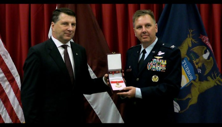 The President of the Republic of Latvia (left) presented Col. J. Andrew Roberts, commander of the Alpena Combat Readiness Training Center, with the Order of Viesturs medal, Sept. 23, 2016, at the Michigan National Guard headquarters facility in Lansing. The Order of Viesturs is presented only by the President and was given to Roberts to recognize his efforts toward strengthening the country and promoting joint learning between military forces. Roberts served as the bilateral affairs officer to Latvia in 2012 and 2013. (Michigan National Guard photo by Angela Simpson/released).