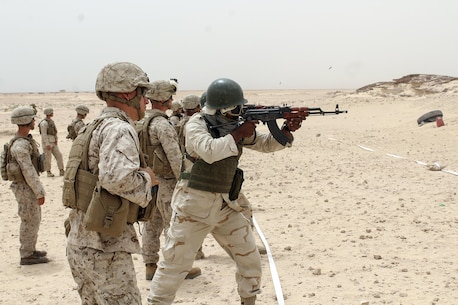 Lance Cpl. Nathaniel Madison, a rifleman with Special Purpose Marine Air-Ground Task Force Crisis Response-Africa, watches a Mauritanian Fusiler Marin fire his weapon while at a rifle range near Rosso, Mauritania, Aug. 29, 2016. Marines worked on small unit tactics, detainee procedures, weapons handling and marksmanship techniques while training with the Mauritanian FUMA to aid in the suppression of illicit trafficking in the region.  (U.S. Marine Corps courtesy photo/released)