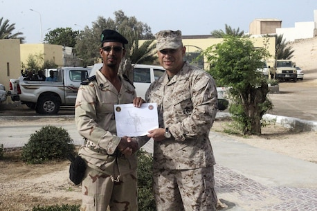 Capt. Felipe Rodriguez, a company commander with Special Purpose Marine Air-Ground Task Force Crisis Response-Africa, holds a certificate of completion with a Mauritanian Fusiler Marin following a graduation ceremony near Rosso, Mauritania, Sept. 23, 2016. Marines worked on small unit tactics, detainee procedures, weapons handling and marksmanship techniques while training with the Mauritanian FUMA to aid in the suppression of illicit trafficking in the region.  (U.S. Marine Corps courtesy photo/released)