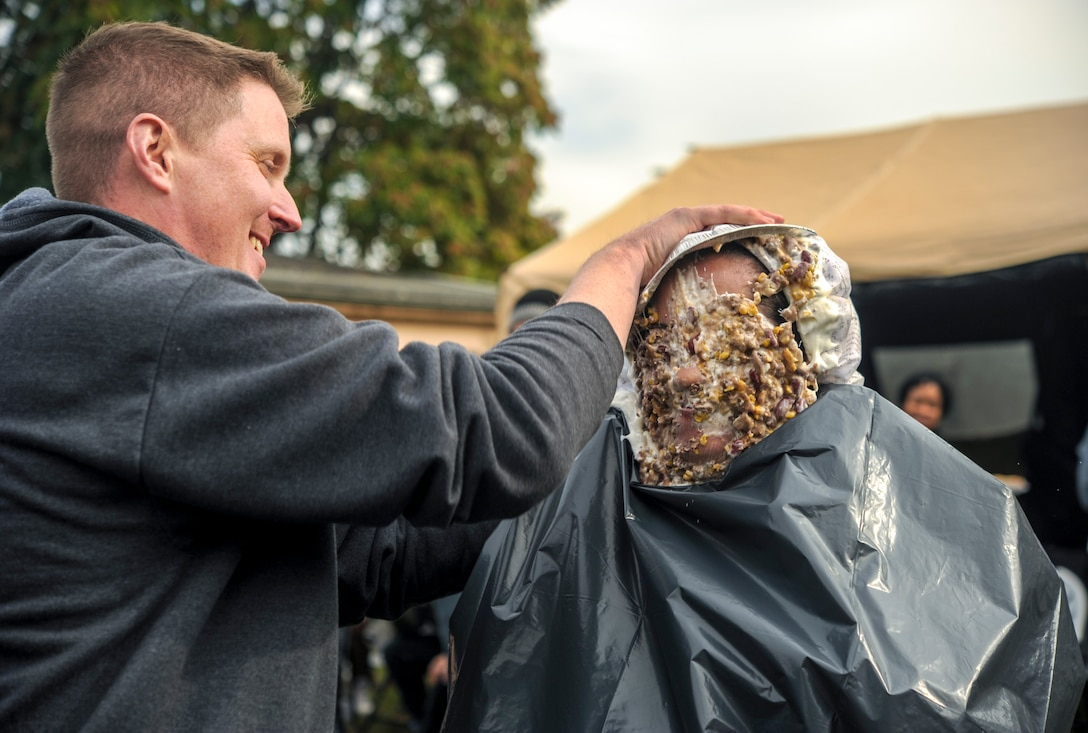 """Maj. Reed Reichwald, 693rd Intelligence, Surveillance and Reconnaissance Group operational psychologist, spreads a """"mutton"""" pie over the head of Lt. Col. Ariel Batungbacal, 450th Intelligence Squadron commander, during the Pie-in-the-Face portion of the 693rd ISRG's 5th Annual Highland Games in Wiesbaden, Germany, Oct. 14, 2016. Members of the 693rd ISRG donated money to have other members of the group hit in the face with a pie. All proceeds raised for the event were donated to the Combined Federal Campaign-Overseas. (U.S. Air Force photo by Staff Sgt. Timothy Moore)"""