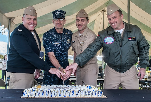 (From left) Navy Capt. Justin DeBord, Navy Capt. Jeffrey Schmidt, Lt. Cmdr. Michael Sargent, and Navy Capt. Brian Ginnane slice the cake at the Navy's 241st birthday celebration Oct. 13 at Defense Supply Center Columbus. Schmidt and Sargent represented the oldest and youngest, respectively, sailors in attendance.