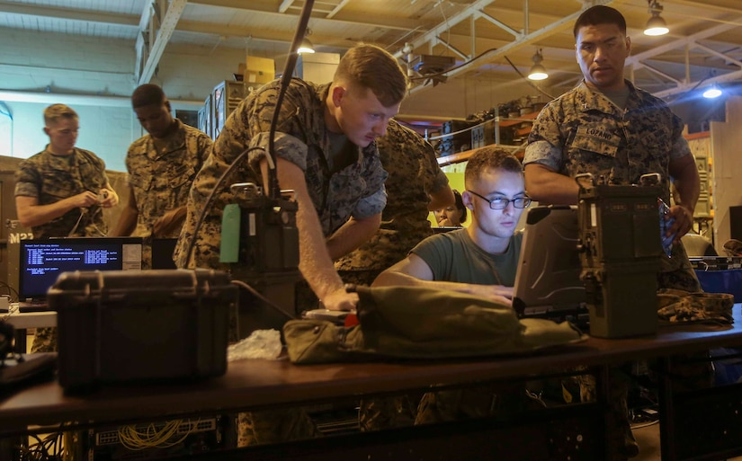 Marines learn how to connect a radio to a computer during a training exercise at Camp Lejeune, N.C., Oct. 17, 2016. Four units where present for Adaptive Network Wideband Waveform training, which focused on the units configuring their equipment in order to communicate with each other without an internet service. The Marines come from various communication specialties within 2nd Marine Logistics Group. (U.S. Marine Corps photo by Lance Cpl. Ashley Lawson)