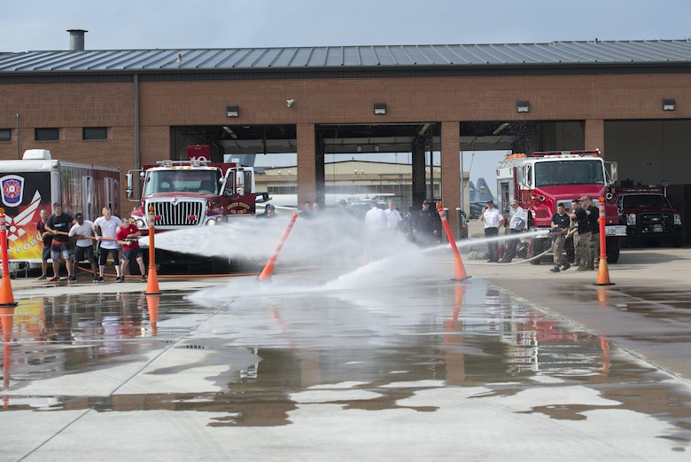 A team of Airmen from the 82nd Medical Group and the 82nd Security Forces Squadron, compete head-to-head in the Sheppard Air Force Base, firefighter challenge, Oct. 14, 2016. Each team had to knock over the cones in their lanes with the fire hose in-order to progress to the next challenge. (U.S. Air Force photo by Senior Airman Kyle E. Gese)