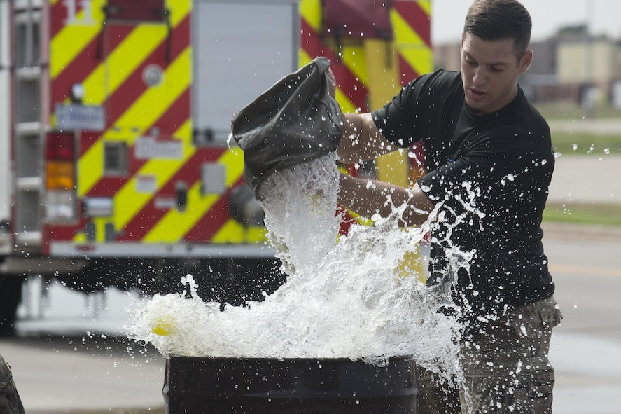 Senior Airman Carmen Pontello, 82nd Security Forces Squadron defender, rapidly fills an oil drum during the Sheppard Air Force Base, Texas, firefighter challenge, Oct. 14, 2016. The bucket brigade challenge involves transporting water from a nearby reservoir, to an empty oil drum. Each team must fill the drum until balls floating inside overflow. (U.S. Air Force photo by Senior Airman Kyle E. Gese)