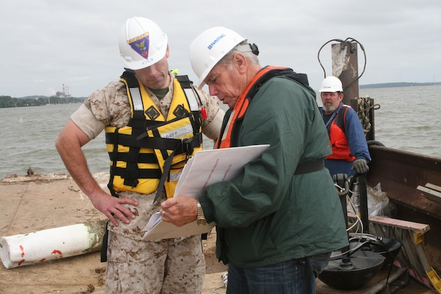 Lt. Col. William Pacatte, commanding officer of Marine Corps Air Facility Quantico (MCAF), and Dale Synnes, Naval Facilities Engineering Command, examine the plans for the installation of buoys marking restricted waters offshore of MCAF on Oct. 5.