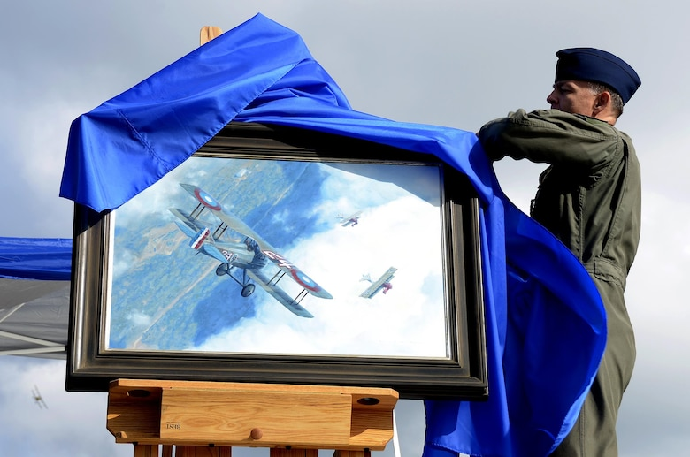 Senior Master Sgt. Darby Perrin, an Air Force artist from the 465th Air Refueling Squadron, Tinker Air Force Base, Oklahoma, unveils his painting at the Dawn Patrol Rendezvous event held at the National Museum of the United States Air Force in Ohio, Oct. 1, 2016. The painting depicts 1st Lt. Charles d'Olive's victory over three German fighter planes during World War I. (U.S. Air Force photo/Staff Sgt. Joel McCullough)