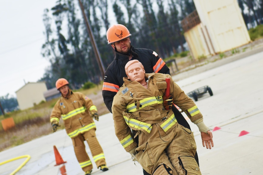 Senior Airman Adam Schaefer, 30th Civil Engineer Squadron fire engineer, completes a dummy drag as he trains for the Scott Firefighter Combat Challenge while Senior Master Sgt. Bronson Peters, 30th CES deputy fire chief, coaches him in the background, Aug. 20, 2016, Vandenberg Air Force Base, Calif.  This year the team from Vandenberg had many first time competitors, including Schaefer who was awarded the 'Greenhorn' award for the fastest first time run. (U.S. Air Force photo by Senior Airman Ian Dudley/Released)