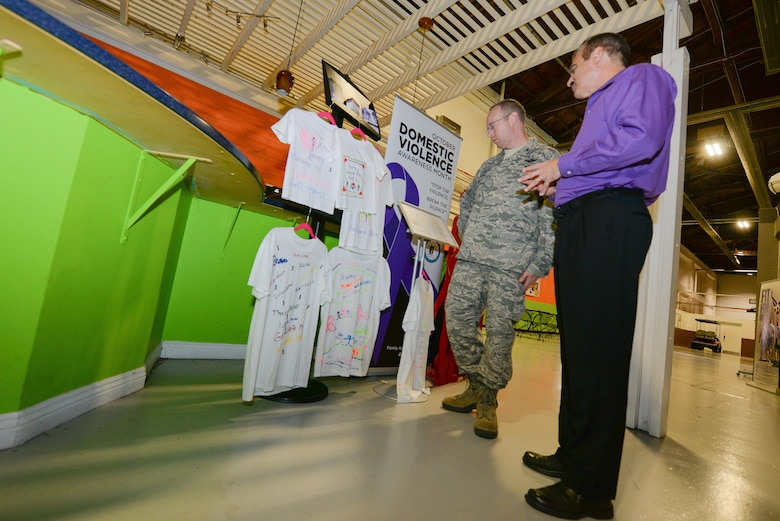 U.S. Air Force Col. David Berg (left), 55th Wing vice commander, talks with Kenneth Komyathy, family advocacy director, about the display set up to support Domestic Violence Awareness month in the Offutt Field House at Offutt Air Force Base, Neb., Oct. 18, 2016. October is Domestic Violence Awareness month, a time of year to bring awareness to domestic violence issues and available resources. (U.S. Air Force photo by Zachary Hada)