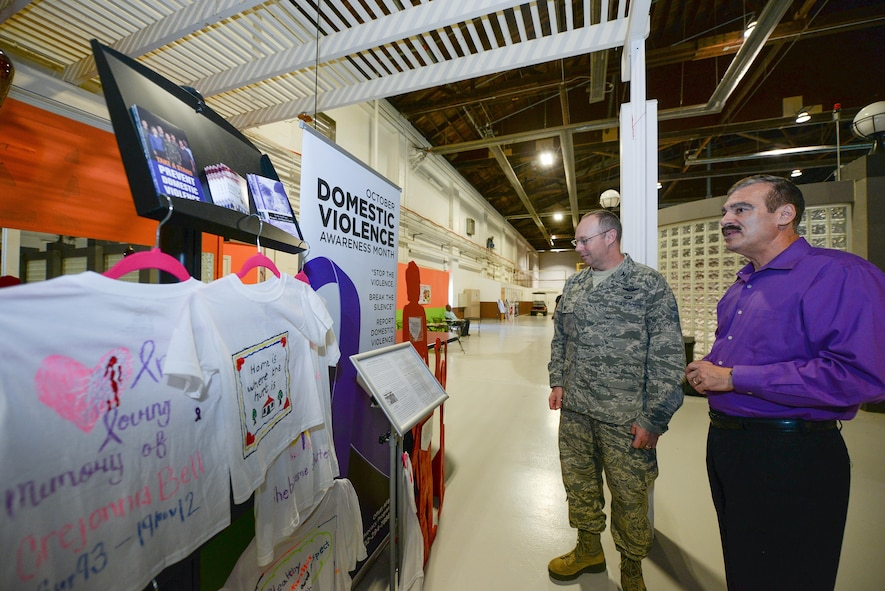 U.S. Air Force Col. David Berg (left), 55th Wing vice commander, talks with Kenneth Komyathy, family advocacy director, about the display set up to support Domestic Violence Awareness month in the Offutt Field House at Offutt Air Force Base, Neb., Oct. 18, 2016. According to the Department of Defense, domestic violence is an offense under the United States Code, the Uniform Code of Military Justice or state law that involves the use, attempted use, threat, use of force, violence against a person who is a current or former spouse, a person who shares a child with the abuser, a current or former intimate partner with whom the abuser shares a common domicile. (U.S. Air Force photo by Zachary Hada/Released)