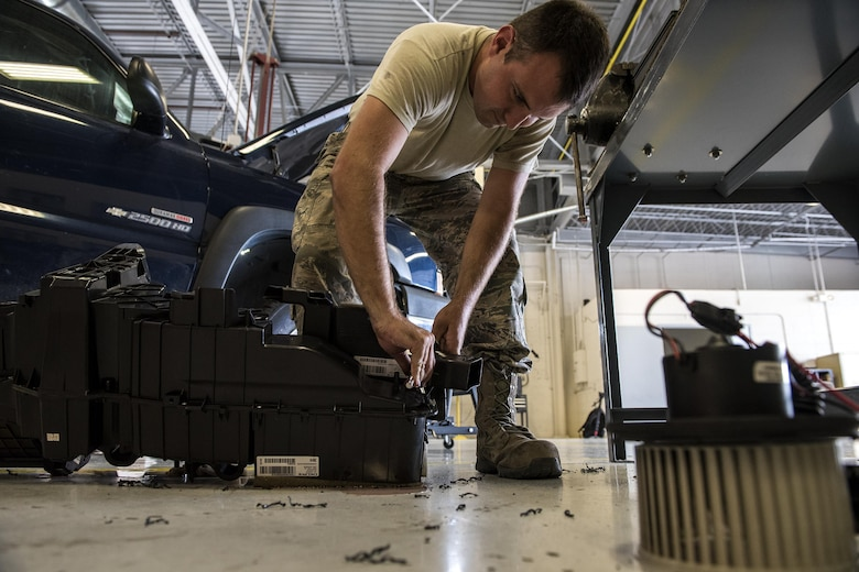Staff Sgt. Adam Hix, 23d Logistics Readiness Squadron vehicle maintenance technician, replaces screws on an air conditioning and heating housing unit, Oct. 12, 2016, at Moody Air Force Base, Ga. Technicians replaced the air conditioning housing unit in the truck because the previous one shattered. (U.S. Air Force photo by Airman 1st Class Janiqua P. Robinson)