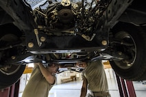 Senior Airman Corbin Mellor, left, and Airman 1st Class Gavin McClaskey, 23d Logistics Readiness Squadron vehicle maintenance technicians, search for bolts connected to an engine, Oct. 12, 2016, at Moody Air Force Base, Ga. After loosening the bolts, the technicians removed the V6 engine to replace and repair the assembly that connects the crank shaft to the camshaft. (U.S. Air Force photo by Airman 1st Class Janiqua P. Robinson)