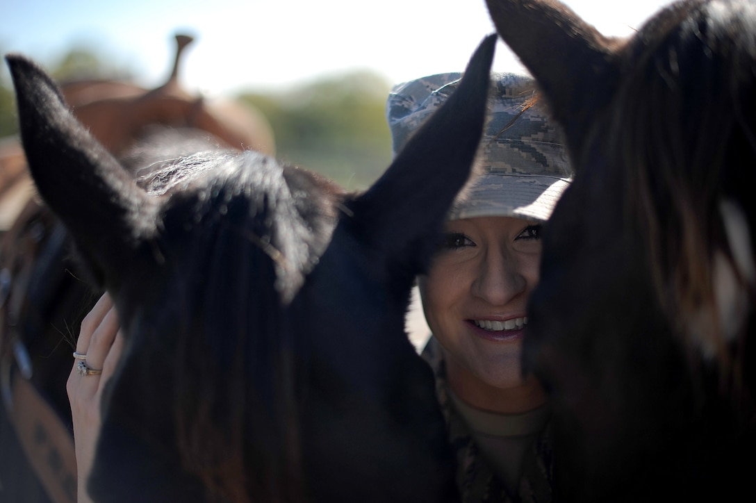 Airman 1st Class Lauren Nolan, 22nd Logistics Readiness Squadron materials management journeyman, poses for a photo with her horses, Tiz and Shoobie, Oct. 13, 2016, in Wichita, Kan. Nolan brings Airmen out to visit with the horses, in hopes of helping the Airmen decrease stress and build resiliency. (U.S. Air Force photo/ Airman 1st Class Jenna K. Caldwell)