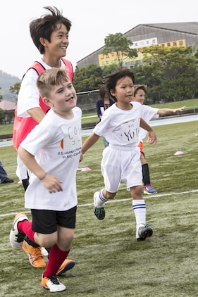 """Children run around for a warm-up during a game of Doro-kei prior to playing soccer at the U.S.-Japan Children Soccer event at the Suo-Oshima Athletic Field in Suo-Oshima, Japan, Oct. 1, 2016. Doro-kei is a game similar to the American """"Cops and Robbers"""". Participating in the event gave the children an opportunity to learn new things. (U.S. Marine Corps photo by Lance Cpl. Joseph Abrego)"""
