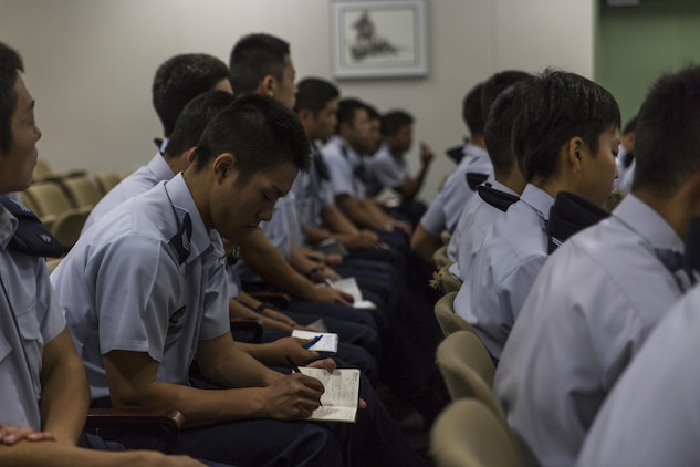 Japan Air Self-Defense Force aviation cadets with the 12th Flight Training Wing from JASDF Hōfu-kita Air Base takes notes during a Japanese officer engagement program at Marine Corps Air Station Iwakuni, Japan, Oct. 19, 2016. During the visit, approximately 40 cadets toured the air station to see an F/A-18D Hornet assigned to Marine All-Weather Fighter Attack Squadron (VMFA(AW)) 225 and a KC-130J Hercules belonging to Marine Aerial Refueler Transport Squadron (VMGR) 152. Cadets also took turns flying a KC-130J flight simulator and learned about Marine Aircraft Group 12 and the air station. (U.S. Marine Corps photo by Lance Cpl. Aaron Henson)