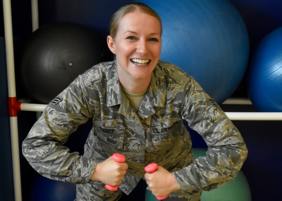 Senior Airman Catherine Libbey, 439th Aeromedical and Dental Squadron, shows off her muscles. Libbey recently passed her fitness test after failing three times and being warned that if she failed again, she would be discharged. (U.S. Air Force photo/ TSgt. Amelia Leonard)