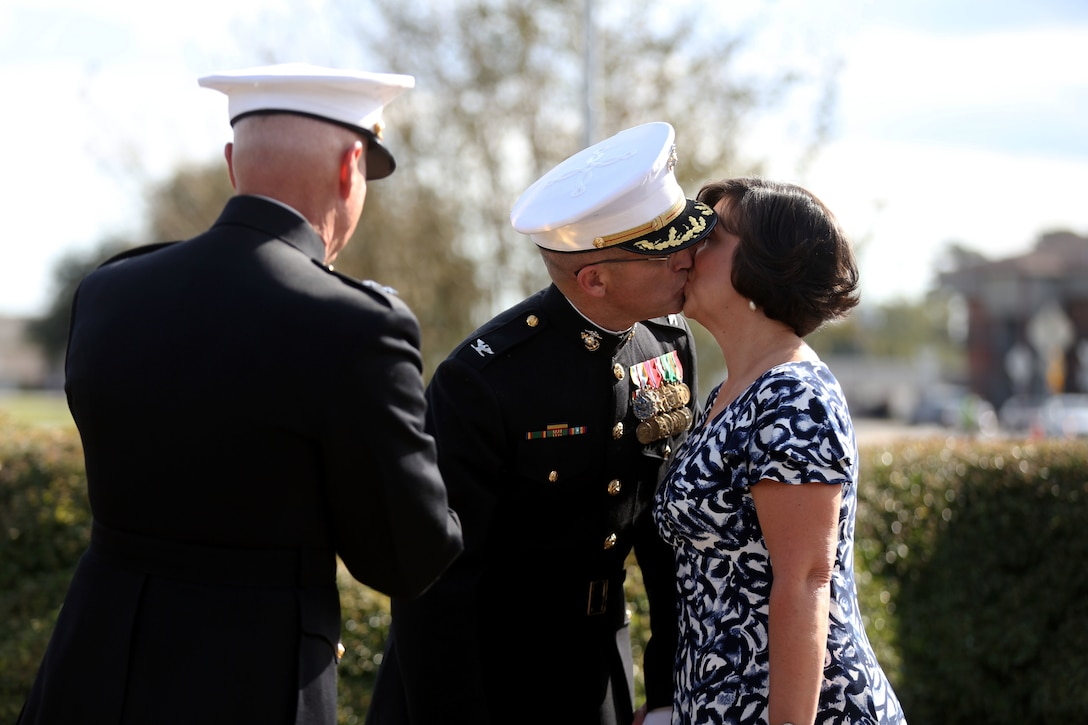 Col. Yori R. Escalante kisses his wife after she receives an award at his side, during his retirement ceremony at Marine Corps Base Camp Lejeune, Oct. 14. Col. Yori R. Escalante, deputy commander of Marine Corps Installation East - Marine Corps Base Camp Lejeune, retired today  after 30 years of faithful and dedicated service to the Marine Corps. (U.S. Marine Corps photo by Pfc. Juan Madrigal/Released)