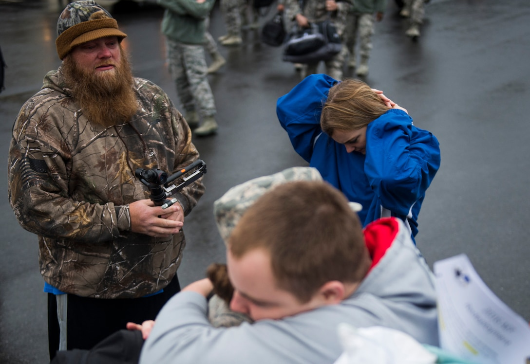 A husband watches as his wife, an Airman assigned to the 606th Air Control Squadron, greets family during the squadron's return to Spangdahlem Air Base, Germany, Oct. 20, 2016. The 606th ACS is a self-sustaining squadron consisting of maintenance, supply and approximately 21 other Air Force specialties. (U.S. Air Force photo by Airman 1st Class Preston Cherry)