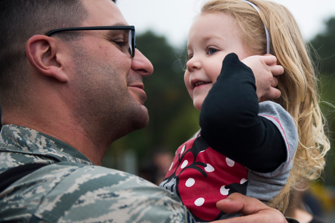 An Airman assigned to the 606th Air Control Squadron reunites with his daughter during the squadron's return to Spangdahlem Air Base, Germany, Oct. 20, 2016. While deployed, the squadron provided support to the 727th Expeditionary Air Control Squadron, also known as Kingpin, which is composed of U.S. and coalition partners who monitor activity in the airspace surrounding their area of responsibility. (U.S. Air Force photo by Airman 1st Class Preston Cherry)