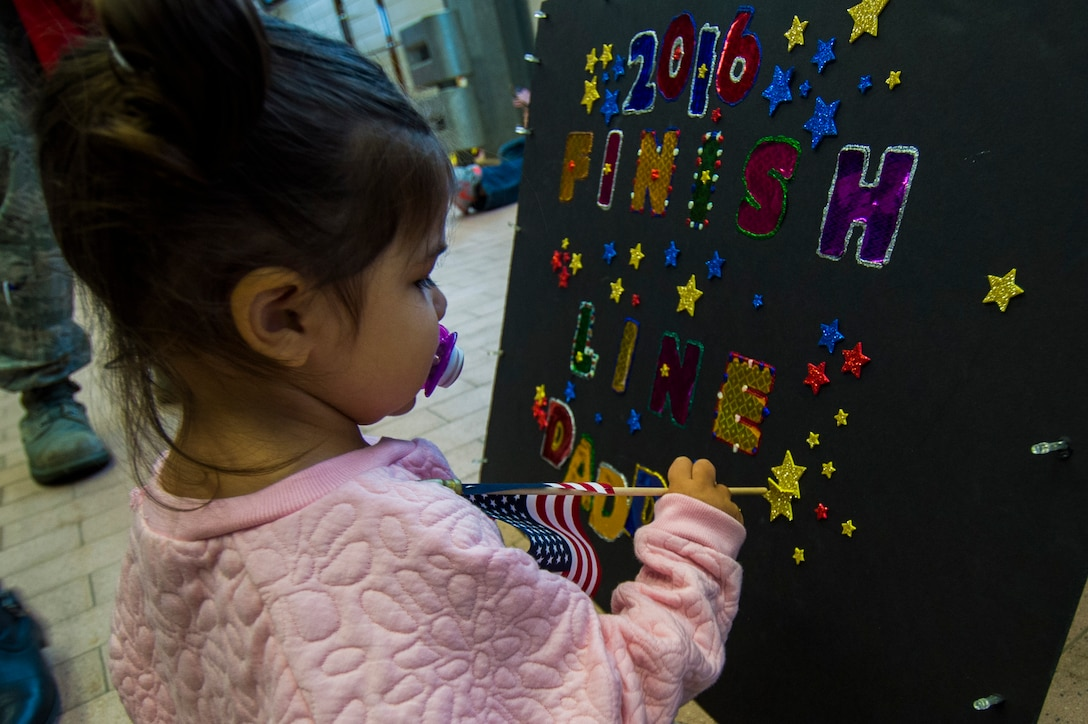 A child of an Airman assigned to the 606th Air Control Squadron awaits her father's return from deployment to their squadron at Spangdahlem Air Base, Germany, Oct. 20, 2016. Nearly 200 Airmen assigned to the 606th ACS returned, from a six-month rotational deployment to Southwest Asia in support of Operations Freedom's Sentinel and Inherent Resolve. (U.S. Air Force photo by Staff Sgt. Joe W. McFadden)