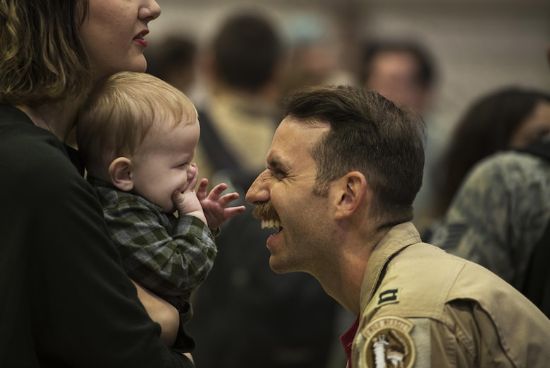 An Airman assigned to the 480th Expeditionary Fighter Squadron reunites with his family during the squadron's return to Spangdahlem Air Base, Germany, Oct. 12, 2016. Approximately 300 of the squadron's Airmen, who serve in flight, maintenance or support roles for the F-16 Fighting Falcon, completed a six-month deployment to Southwest Asia by providing close air support and dynamic targeting operations in support of Operation Inherent Resolve. (U.S. Air Force photo/Staff Sgt. Jonathan Snyder)