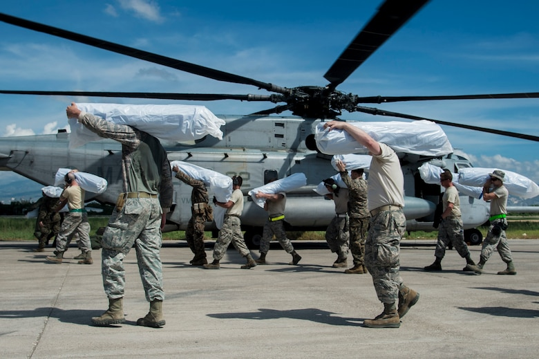 Members of the 621st Contingency Response Wing load humanitarian aid onto a Marine Corps CH-35E Super Stallion in Port-au-Prince, Haiti, Oct. 16, 2016. The 621st CRW has units ready to deploy anywhere in the world within 12 hours of notification in support of emergency operations. (U.S. Air Force photo/Staff Sgt. Robert Waggoner)