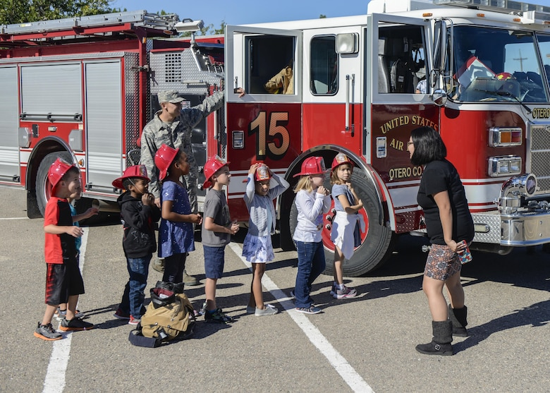 A group of children take turns exploring a fire truck at Holloman Air Force Base's elementary school as part of the base's annual Fire Prevention Week, Oct. 14, 2016 at Holloman AFB, N.M. Holloman AFB firefighters visited the base's elementary and middle schools throughout the week, to teach students about the importance of practicing fire safety. (U.S. Air Force photo by Airman 1st Class Alexis P. Docherty)