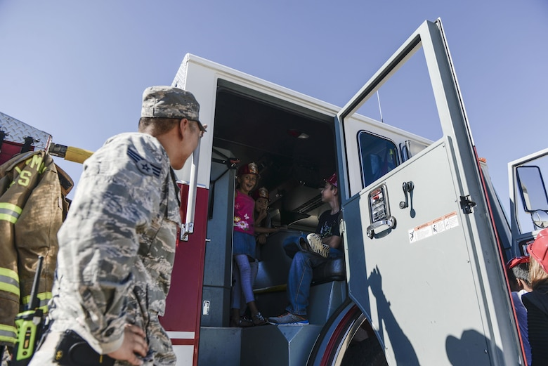 A group of children sit inside a fire truck at Holloman Air Force Base's elementary school as part of the base's annual Fire Prevention Week, Oct. 11, 2016 at Holloman Air Force Base, N.M. Sparky the Fire Dog and members with the 49th Civil Engineer Squadron Fire Protection Flight, educated students on fire safety and allowed them to explore two fire trucks. (U.S. Air Force photo by Airman 1st Class Alexis P. Docherty)
