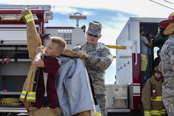A firefighter with the 49th Civil Engineer Squadron Fire Protection Flight helps a student at Holloman Air Force Base's middle school put on a flame retardant suit as part of the base's annual Fire Prevention Week, Oct. 13, 2016 at Holloman AFB, N.M. Holloman firefighters taught students about fire safety and prevention, and showcased firefighting equipment to them. (U.S. Air Force photo by Airman 1st Class Alexis P. Docherty)