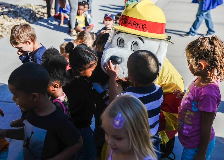A group of children greet Sparky the Fire Dog during a visit to the child development center as part of Holloman Air Force Base's annual Fire Prevention Week, Oct. 14, 2016. Members of the 49th Civil Engineer Squadron Fire Protection Flight also visited the center to teach children about fire safety and prevention. (U.S. Air Force photo by Airman 1st Class Airman Alexis P. Docherty)