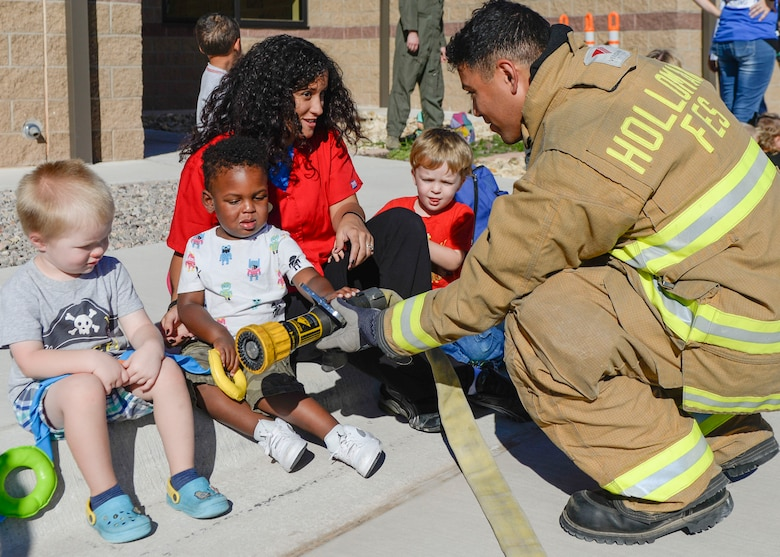 A firefighter with the 49th Civil Engineer Squadron Fire Protection Flight shows three children a fire hose during a visit at the child development center as part of Holloman Air Force Base's annual Fire Prevention Week, Oct. 14, 2016. Sparky the Fire Dog and members of the 49th Civil Engineer Squadron Fire Protection Flight visited the center to spread awareness about fire safety. (U.S. Air Force photo by Airman 1st Class Alexis P. Docherty)
