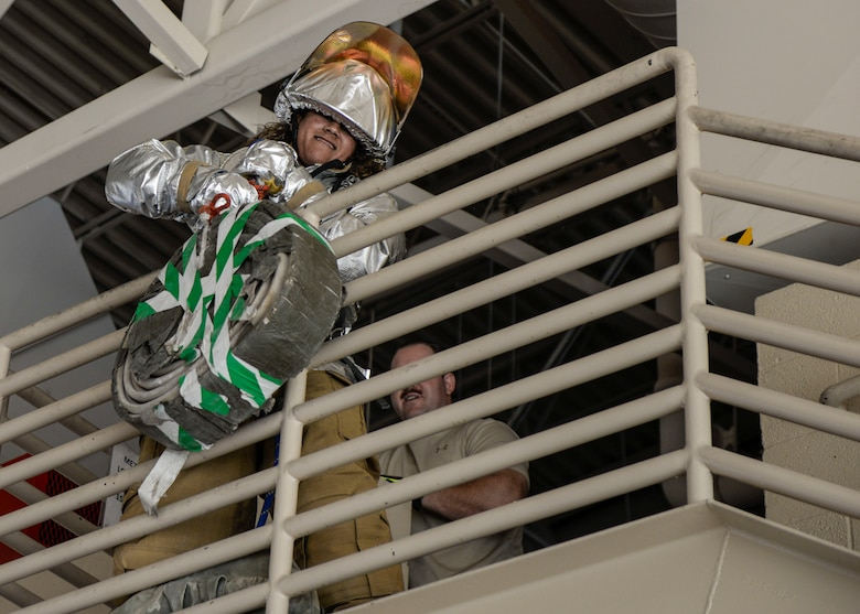 A competitor yanks a high rise pack overtop a stairwell railing during a firefighter muster challenge, as part of Holloman Air Force Base's annual Fire Prevention Week, Oct. 14, 2016 at Holloman AFB, N.M. The firefighter muster challenge is designed to simulate the various physical stressors that firefighters encounter on a daily basis. Competitors were fitted in flame retardant suits and raced against the clock to complete a variety of tasks, including dummy drags and hose pulls. (U.S. Air Force photo by Airman 1st Class Alexis P. Docherty)