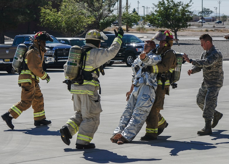A competitor performs a body drag during the firefighter muster challenge, as part of Holloman Air Force Base's annual Fire Prevention Week, Oct. 14, 2016 at Holloman AFB, N.M. Competitors were fitted in flame retardant suits and raced against the clock to complete a variety of intense physical tasks, which are meant to simulate the stressors that firefighters encounter on a daily basis. (U.S. Air Force photo by Airman 1st Class Alexis P. Docherty)