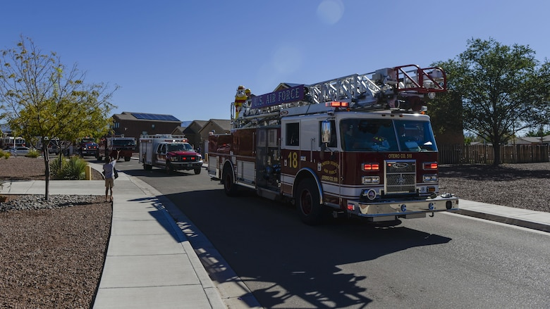 A child waves to an ambulance during Holloman Air Force Base's annual Fire Prevention Week parade through the Soaring Heights community, Oct. 15, 2016 at Holloman AFB, N.M. Sparky the Fire Dog and members of the 49th Civil Engineer Squadron Fire Protection Flight drove through several base neighborhoods and gifted candy to children and families. (U.S. Air Force photo by Airman 1st Class Alexis P. Docherty)