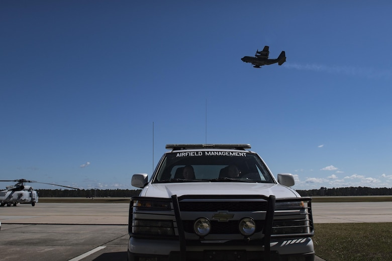 Tech. Sgt. Shannon Walsh, left, 23d Operations Support Squadron NCO in charge of airfield management operations and Senior Airman Kelsey Seroogy, 23d OSS airfield management shift leader, park their truck after a routine driven inspection while an HC-130J Combat King II ascends in the background, Oct. 19, 2016, at Moody Air Force Base, Ga. It's safe to say anytime an aircraft is seen in Moody's skies, members of airfield management are manning their stations. (U.S. Air Force photo by Airman 1st Class Daniel Snider)