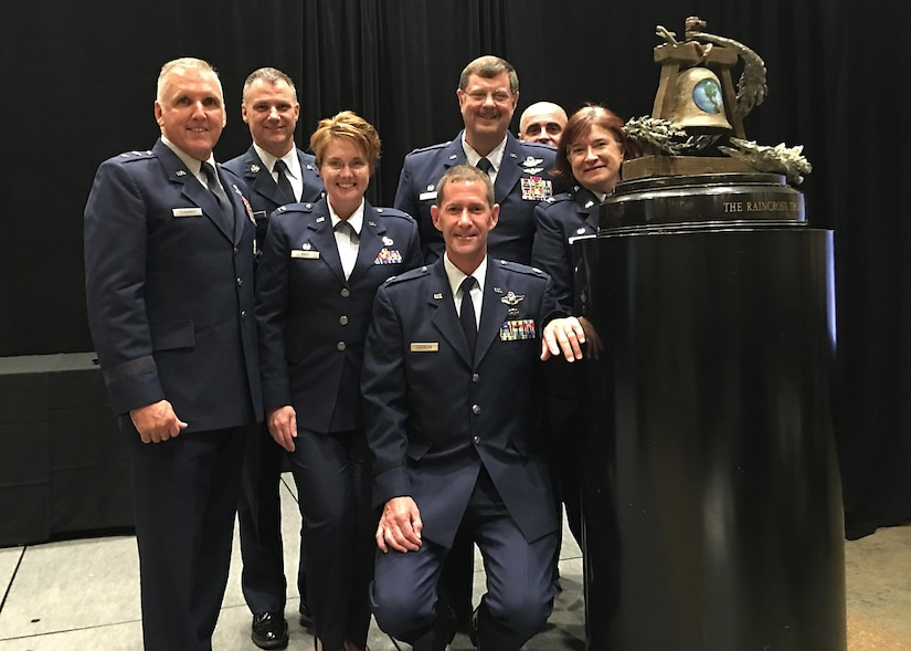 From Left, Maj. Gen. John Flournoy Jr, 4th Air Force commander;  Chief Master Sgt. Mark Barber, 315th Airlift Wing command chief; Col. Cherie Roff, 315th Mission Support Group commander; Lt. Col. John Robinson, 315th Operations Group vice commander (seated); Col. Gregory Gilmour, 315th AW commander; Tech Sgt. Tim Kelly, 315th AW Safety; and Col. Sharon Johnson, incoming 315th Maintenance Group commander, pose with the Raincross Trophy Oct. 20 after the 315th AW received the award at the Raincross Trophy Dinner in Riverside, California. (Courtesy photo)