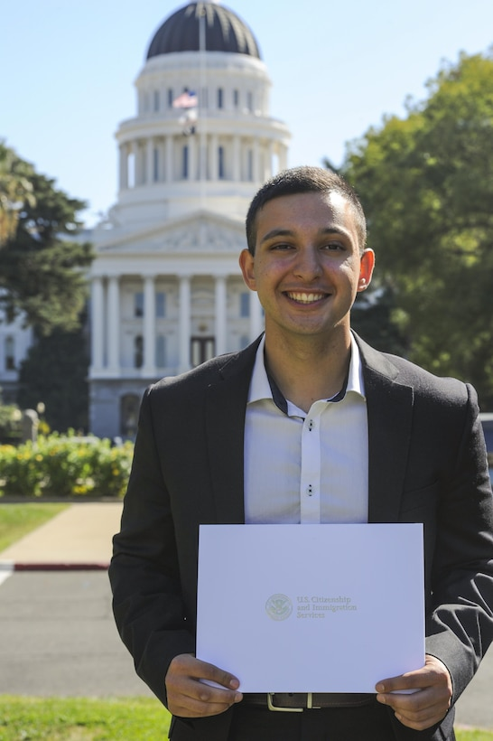 Airman Aris D. Soltani, a 940th Aircraft Maintenance Squadron personnelist, poses for a photo with U.S. citizenship certificate Oct. 11, 2016, in Sacramento, California. Soltani passed his citizenship test and recited the Oath of Allegiance earlier that day. (U.S. Air Force Photo by Senior Airman Tara R. Abrahams)