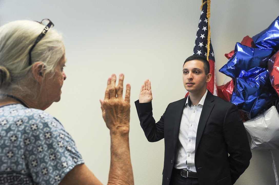 Airman Aris D. Soltani, a 940th Aircraft Maintenance Squadron personnelist, recites the Oath of Allegiance Oct. 11, 2016, in Sacramento, California. Soltani was born in Germany and had been working toward citizenship for almost six years. (U.S. Air Force Photo by Senior Airman Tara R. Abrahams)