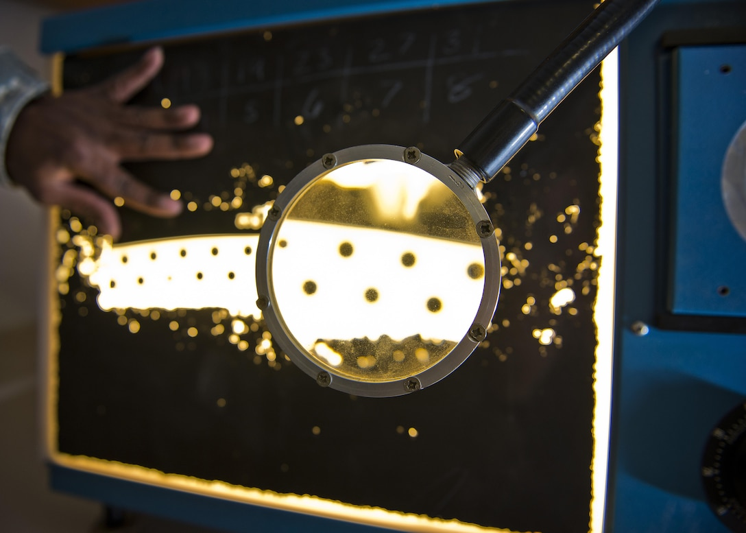 A magnifying glass enlarges a section of x-ray film at Minot Air Force Base, N.D., Oct. 17, 2016. Non-destructive inspection Airmen from the 5th Maintenance Squadron utilize x-rays for inspecting welds on the B-52H Stratofortress. (U.S. Air Force photo/Airman 1st Class J.T. Armstrong)