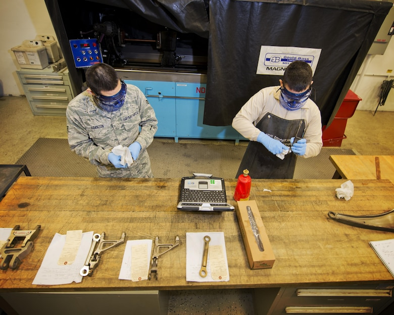 Airmen from the 5th Aircraft Maintenance Squadron clean grease from aircraft parts before a magnetic particle inspection at Minot Air Force Base, N.D., Oct. 18, 2016. All debris and grease are removed to prevent contamination of the particle bath during the inspection process. (U.S. Air Force photo/Airman 1st Class J.T. Armstrong)